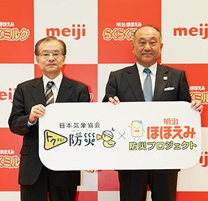 松田克也明治社長(右)と齊藤孝雄日本気象協会理事長