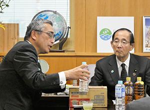 原田義昭環境大臣(右)に「ラベルレスボトル」を説明する岸上克彦社長