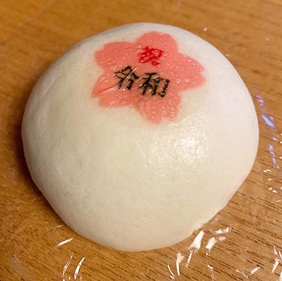 可食性フィルムに食用インクで印刷した「令和」の図柄シールを添付したまんじゅう。わずかな水分と加熱で色鮮やかに蒸着できる