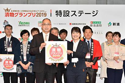 東野昭浩課長(中央左)からグランプリのロゴマークを授与された田口あゆみ係長(同右)