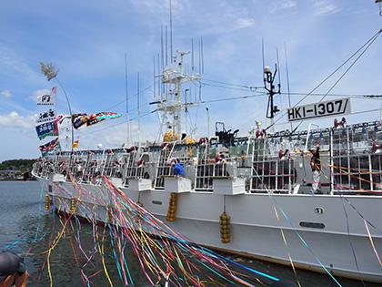 出航式では家族や関係者などがカラーテープを持って見送り。酒田港を一周して、各船が沖合へ出航する