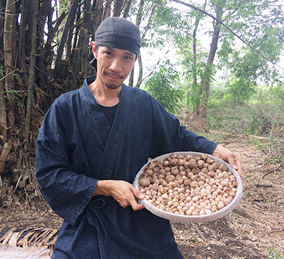 「忍の森」の前で、熟成を終えた黒ニンニクを持つ宮内靖彦さん=提供写真