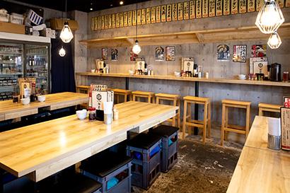 コンクリート壁と白木のカウンターやテーブルを組み合わせてスタイリッシュかつ清潔感あふれる内装を採用。大衆酒場ながら女性客にも高い支持を得ている理由だ