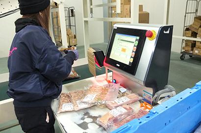 商品投入口で商品データを読み取り、仕分け店舗を認識させる