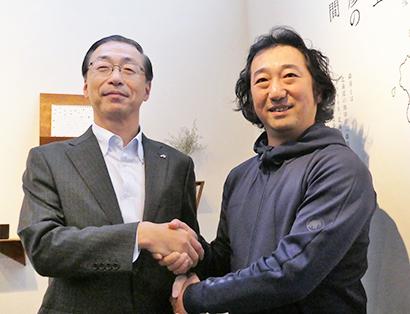 握手する品田英明社長(左)と市川草介アトリエ・モリヒコ代表取締役