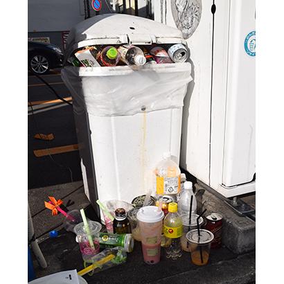自動販売機周辺には、リサイクルボックスに入りきらず放置された飲みかけや容器が散乱する