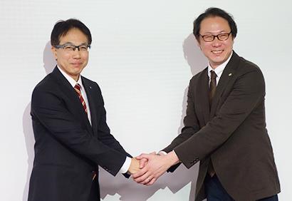 握手するニチレイフーズの安居之雅部長(左)と日立製作所の柳田貴志部長