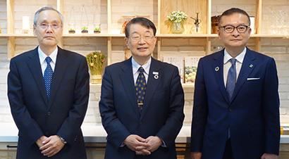 登壇した(右から)金丸哲也専務、中山泰男会長、福間浩一理事長