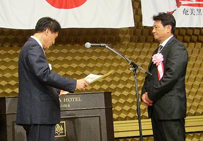 三反園訓鹿児島県知事(左)から表彰される木場修一木場酒造代表取締役