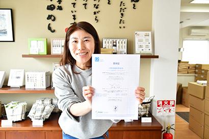 小野製麺は、第1工場・第2工場が国際食品安全規格「FSSC22000 Ver4・1」を取得認定書を手にする同社の水谷理佳さん