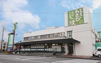 JR静岡駅より車で約15分、国道150号線沿いに立つ田丸屋本店 静岡工場。直売店「ステップインたまるや」も併設されている