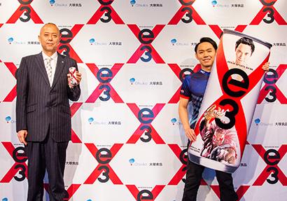 寺田誠司製品部飲料担当部長(左)と「コラボ缶」を手にする「ときど」選手