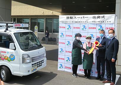ドライバーに記念のキーを渡す小田川浩市長(右から2人目)、山本慎一郎社長(右)