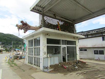ガソリンスタンドの屋根に乗り上げた木(球磨村)