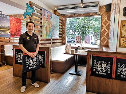 営業中は客席を1テーブルずつ回っているという小澤将生さん=タイ・バンコクで小堀晋一が7月27日写す
