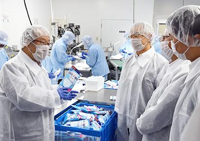 マスク工場で説明する丸谷智保セコマ会長(左)