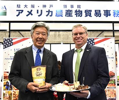 スーパーフードの古代穀物「Maskal Teff Powder」を持つリチャード・メイ・ジュニア総領事(左)とニガキの冷凍ケーキをPRするジェフ・ジマーマンATO大阪所長