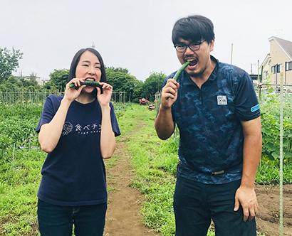 生産者と取れたてのキュウリを食べる秋元里奈社長(左)