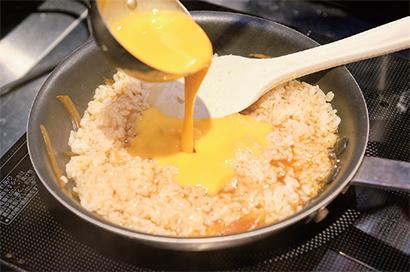 だし汁と割り下で玉ネギを煮て、ライスを加える。溶き卵を混ぜ入れ、サッと絡めると、「つかんと」オリジナルの「カツ丼定食」が完成する