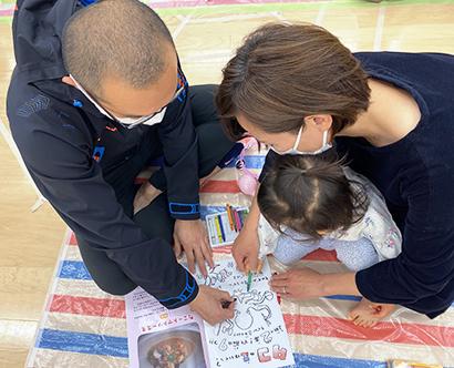 冊子のイラストで塗り絵を楽しむ親子