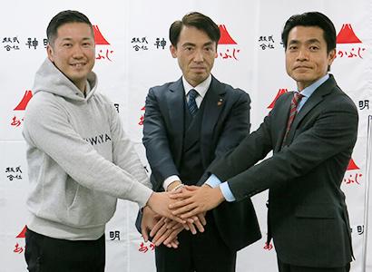 手を重ねる(左から)青木慶哉MIKAWAYA21社長、藤尾益雄神明HD社長、鈴木章人ショクブン社長