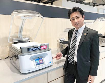 「TOSPACK HOT」HVP―482N(容量5kgまでパック可能)と井上文夫営業本部副本部長。そのほか、容量1kgまでのHVP―282、容量3kgまでのHVP―382Nの3機器をラインアップ