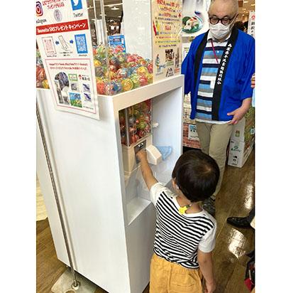 兵庫県手延素麺協同組合、イオン新浦安で販促を 巨大ガチャガチャ登場