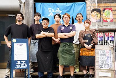 開発に携わった社員7人 手書きの暖簾がかかる「緊急事態製麺 #金獅子」の前にて